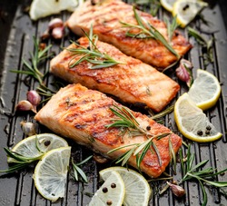 Grilled salmon fillets sprinkled with fresh herbs and lemon juice on a grill plate close up
