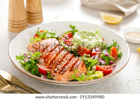 Grilled salmon fish fillet and fresh green lettuce vegetable tomato salad with avocado guacamole.