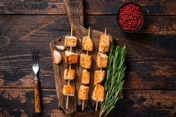 Grilled salmon fish kebab skewers on wooden board. Dark wooden background. Top View