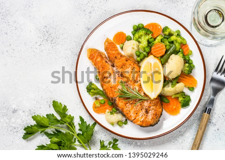 Grilled salmon fish steak with vegetables mix in white craft plate with wine glass. Top view on white stone table.