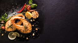 Grilled salmon fish with seasoning and various vegetables on black stone background