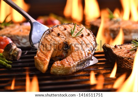 Grilled salmon fish with various vegetables on the flaming grill