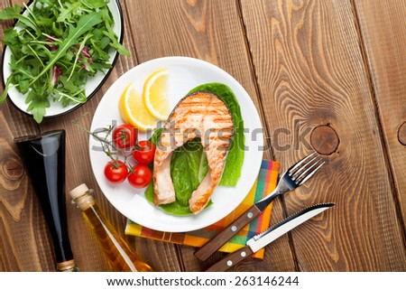 Grilled salmon salad and condiments on wooden table Top view with copy space