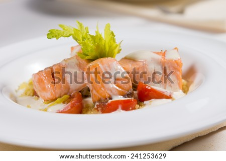 Grilled salmon seafood starter with small portions of fillet, drizzled with a creamy savory sauce and served with lettuce and tomato
