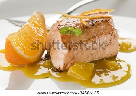 Grilled salmon steak in orange sauce close up