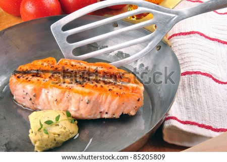 grilled salmon steak with herb butter and pepper in a brass pan