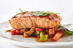 Grilled Salmon Steak with Warm Vegetable Salad Isolated on White Background. Restaurant Main Course with Barbecue Red Fish or Trout Fillet, Greens, Black Pepper and Lime Close Up