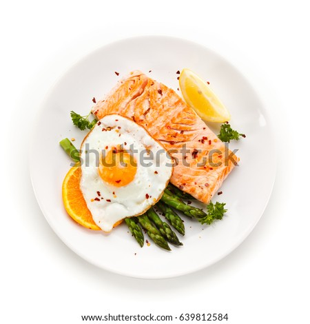 Grilled salmon with asparagus and fried egg on white background  #639812584