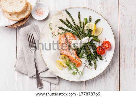 Grilled salmon with asparagus on white wooden background
