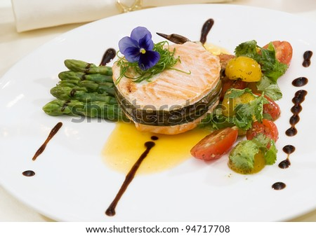 grilled salmon with asparagus,red and yellow tomatoes on white plate