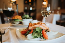 Grilled salmon with mixed salad and avocado cheese burger sitting on table with white table cloth in fine dining restaurant with window light. Film grain look