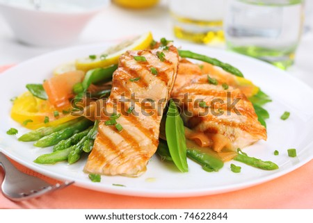 grilled salmon with spring vegetables on white plate, soft focus