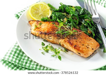 grilled salmon with thyme, lemon and spinach on a plate, vegetarian low carb dish, green napkin on a white background, selected focus, narrow depth of field #378526132