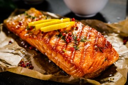Grilled salmon with vegetables served on black stone plate on wooden table