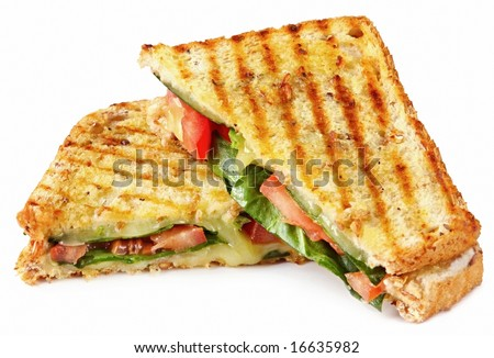 Grilled sandwich or panini with melting cheese, tomato, and spinach leaves, on wholewheat bread. - stock photo