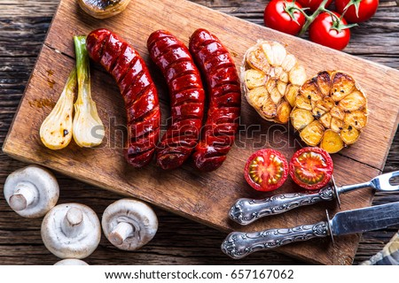 Grilled sausage with mushrooms garlic tomatoes and onions.