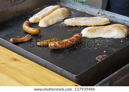 Grilled sausages and bread over black grill
