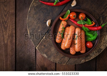 Grilled sausages and vegetables on a wooden background in rustic style. Top view. Flat lay