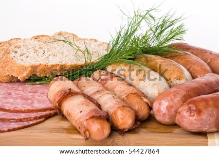 Grilled sausages on a wooden plate with bread and dill