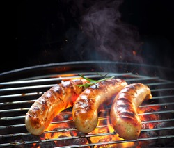 Grilled sausages on grill with smoke and flame on dark background