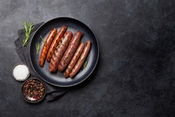 Grilled sausages with rosemary herbs. Top view with copy space