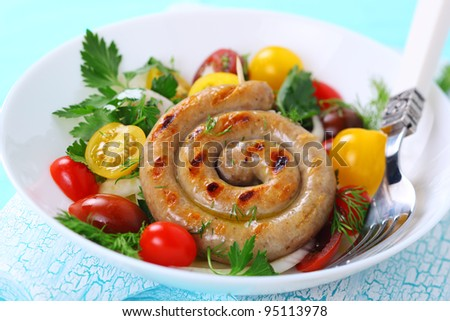 Grilled sausages with salad of tomato-colored on white plate