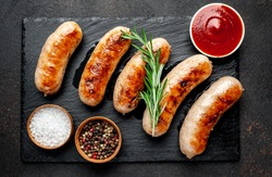 grilled sausages with spices on a stone background