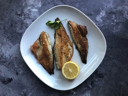 Grilled sea bass fillets with lemon on stone background. Copy space for text.