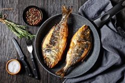 grilled sea bream, orata, dorado fish in a skillet on a dark wooden table with a fork, rosemary and peppercorn, horizontal view from above, flat lay