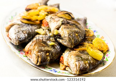 Grilled seabass with vegetables, herbs and lemon on a dish