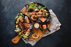 grilled seafood platter. Assorted delicious grilled seafood with vegetables. Grilled mixed bastards with pepper sauce and vegetables. Blue background