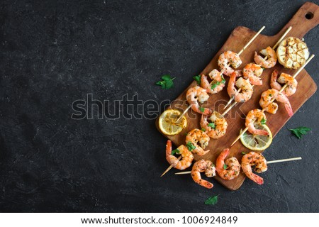 Grilled shrimp skewers. Seafood, shelfish. Shrimps Prawns skewers with herbs, garlic and lemon on black stone background, copy space. Shrimps prawns brochette kebab. Barbecue srimps prawns.
