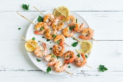 Grilled shrimp skewers. Seafood, shelfish. Shrimps Prawns skewers with spices and fresh herbs on white wooden background, copy space. Shrimps prawns brochette kebab. Barbecue srimps prawns.