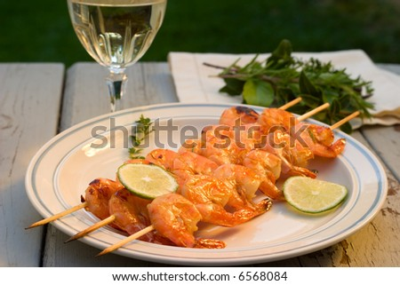 Grilled shrimps on bamboo sticks served with limes, thyme twig and glass of white wine are served outside