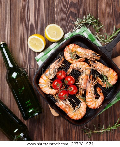Grilled shrimps on frying pan and beer on wooden table. Top view #297961574