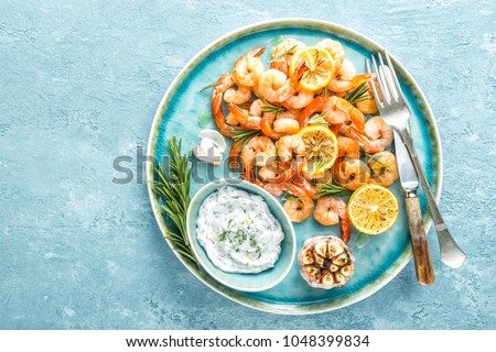 Grilled shrimps or prawns served with lemon, garlic and sauce. Seafood. Top view.