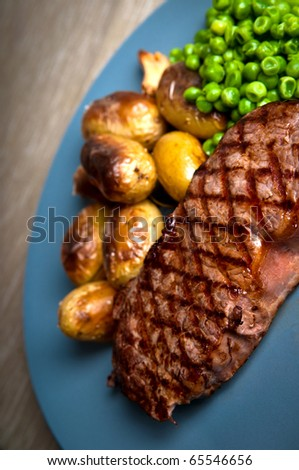 Grilled sirloin steak with rosemary potatoes and peas