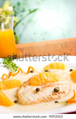 Grilled skate (ray) with orange and caper sauce served with orange juice.