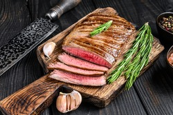 Grilled skirt beef meat steak on a wooden cutting board. Black wooden background. Top view.