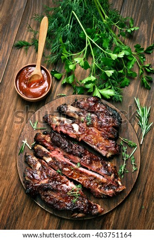 Grilled sliced barbecue pork ribs on wooden background, top view