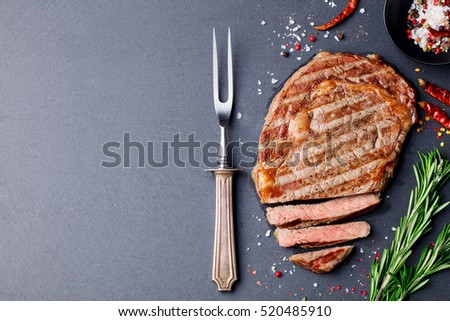 Grilled sliced beef steak on slate stone table. Top view. Copy space