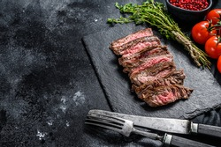 Grilled sliced flank steak with seasonings and spices. Black background. Top view. Copy space