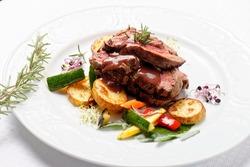 Grilled sliced roast beef on potato and salad