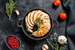 Grilled sliced Turkey steaks in a pan. Breast fillet. Black background. Top view
