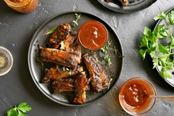 Grilled spare ribs on plate over black stone background. Tasty bbq meat. Top view, flat lay