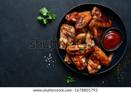 Grilled spicy chicken wings with ketchup on a black plate on a dark slate, stone or concrete background. Top view with copy space.