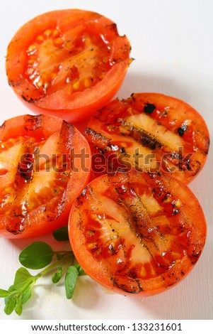 Grilled spicy tomato slices on a white cutting board