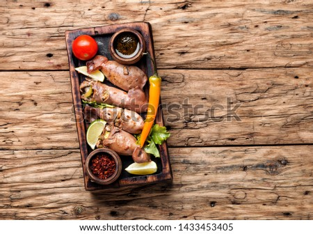 Grilled squid stuffed with vegetables.Seafood on wooden table.Baked squid