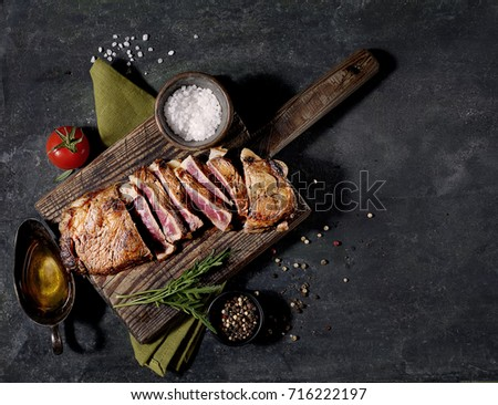 grilled steak and basil on a cutting board