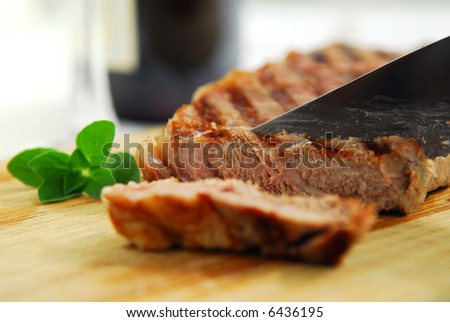 Grilled steak being cut on a cutting board - stock photo